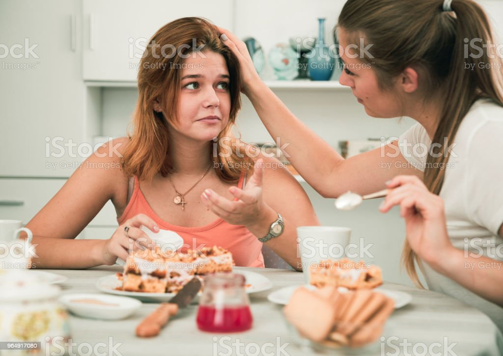 Female talking with young sad friend at home royalty-free stock photo