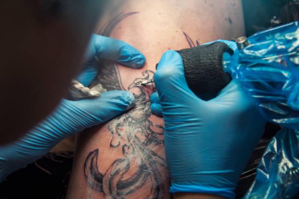 weibliche tattoo-künstler machen tätowierung auf einem männer schulter - vogel phönix tattoos stock-fotos und bilder