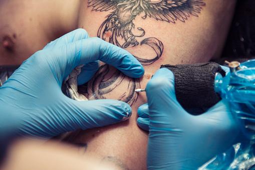 istock Female tattoo artist making tattoo on a men's shoulder 949427002