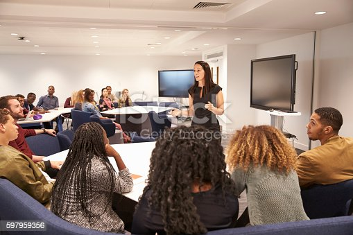 istock Female teacher addressing university students in a classroom 597959356
