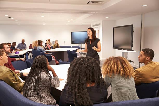 female teacher addressing university students in a classroom - 成年人 個照片及圖片檔