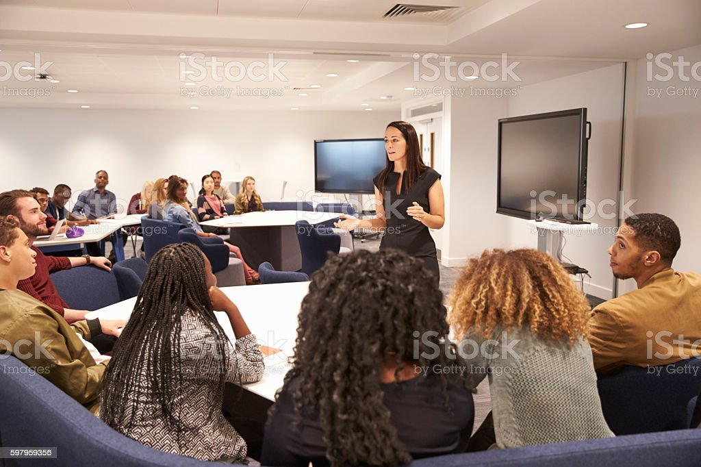 Female teacher addressing university students in a classroom стоковое фото