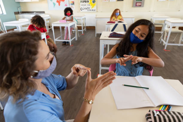 Female teacher and girl wearing face masks talking to each other through sign language in class stock photo
