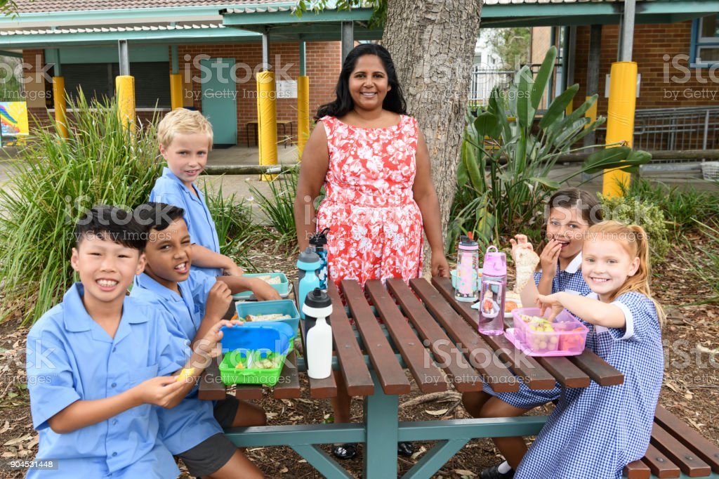 Female teacher and group of school children enjoying lunch outside in playground stock photo