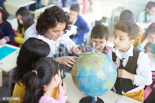 istock female teacher and students looking the globe with a magnifying glass in the classroom 914272880