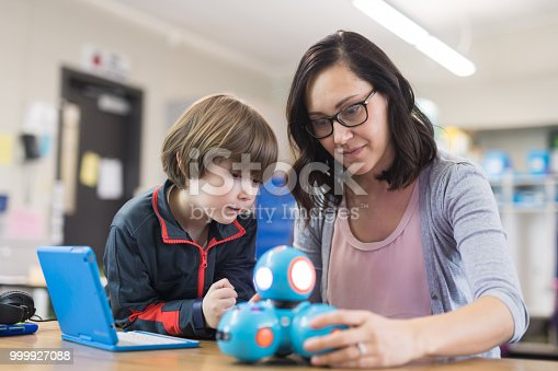 An ethnic female teacher sits next to a first grade boy and helps show him how to program a robot using a digital tablet.