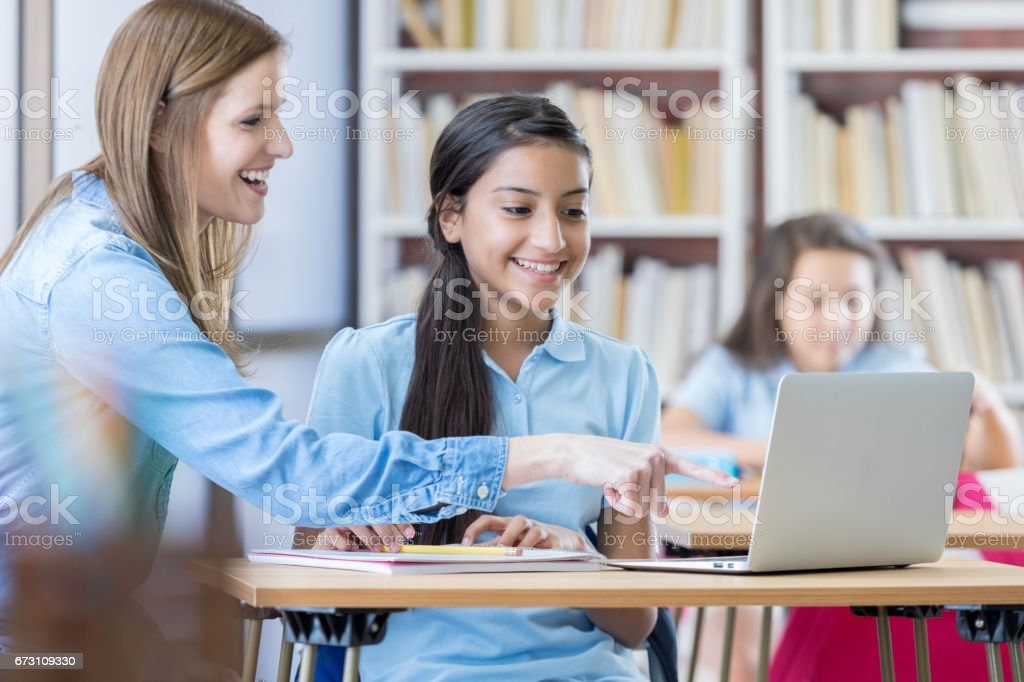Female teacher helps student in technology class stock photo