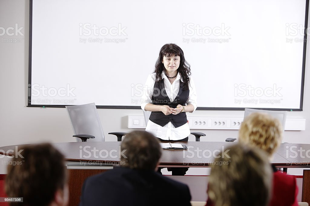 Female teacher in front of aged students stock photo