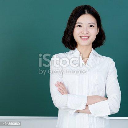 istock Female teacher in front of chalkboard 494850960