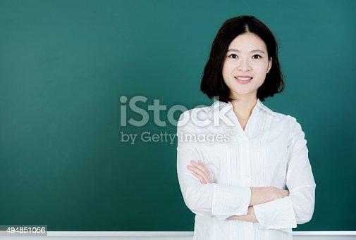 istock Female teacher in front of chalkboard 494851056