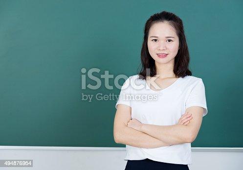 istock Female teacher in front of chalkboard 494876954