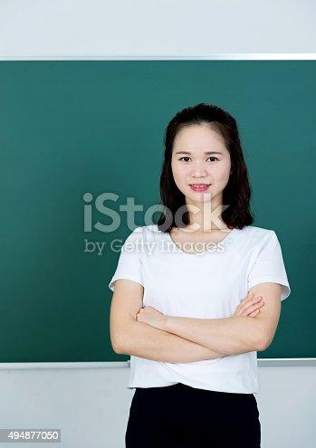 istock Female teacher in front of chalkboard 494877050