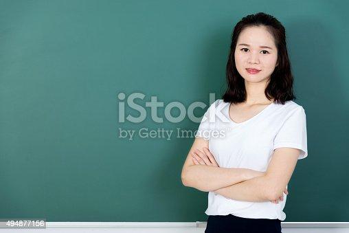 istock Female teacher in front of chalkboard 494877156