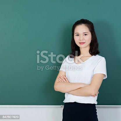 istock Female teacher in front of chalkboard 542927620
