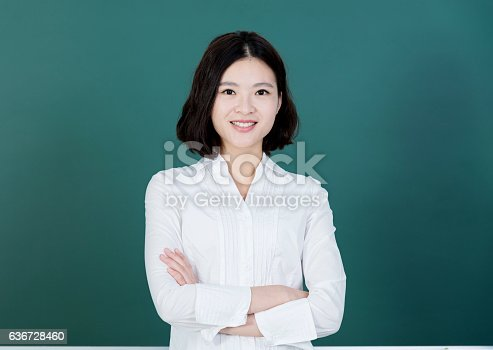 istock Female teacher in front of chalkboard 636728460