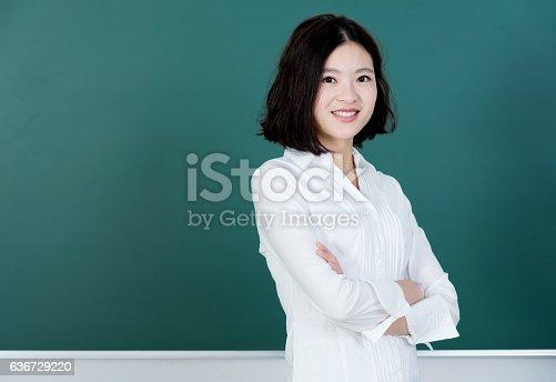 istock Female teacher in front of chalkboard 636729220