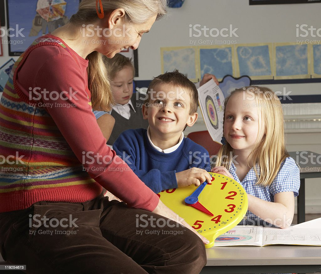 Female Teacher In Primary School Teaching Children To Tell Time royalty-free stock photo
