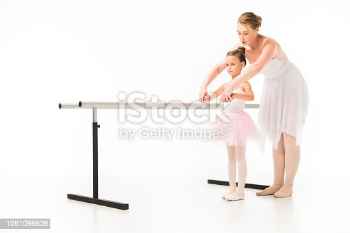 466300721 istock photo female teacher in tutu helping little ballerina practicing at ballet barre stand isolated on white background 1051098626