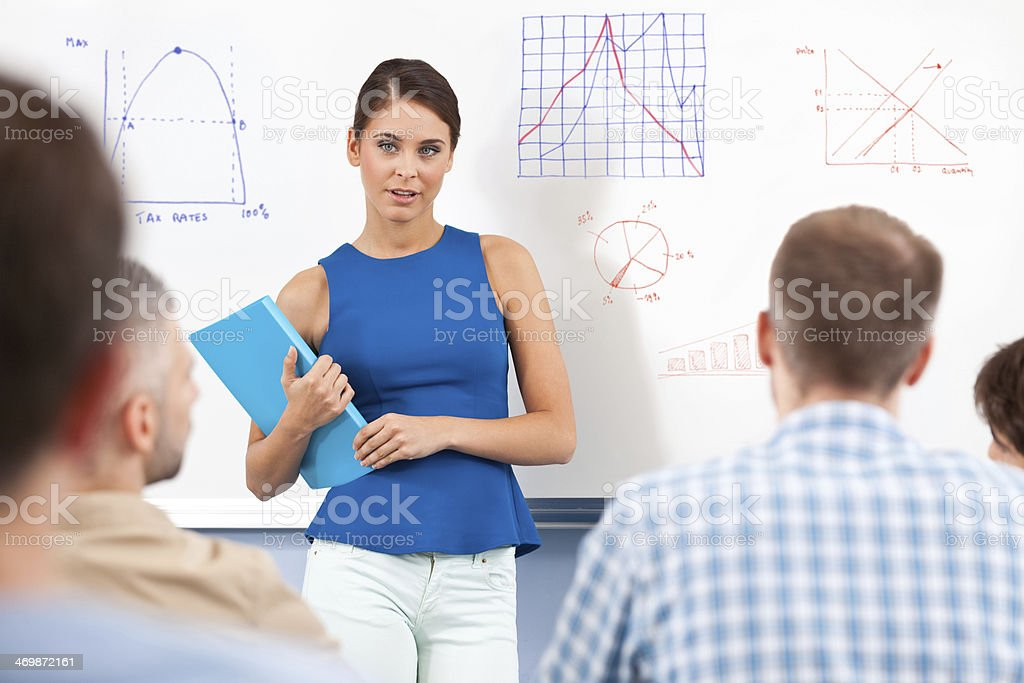 Female teacher Group of adult student attending a job training. Focus on female teacher standing with notebook in front of whiteboard. 30-39 Years Stock Photo