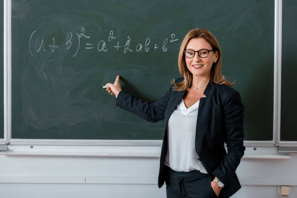 female teacher pointing with finger at mathematical equation on chalkboard in class - professore foto e immagini stock
