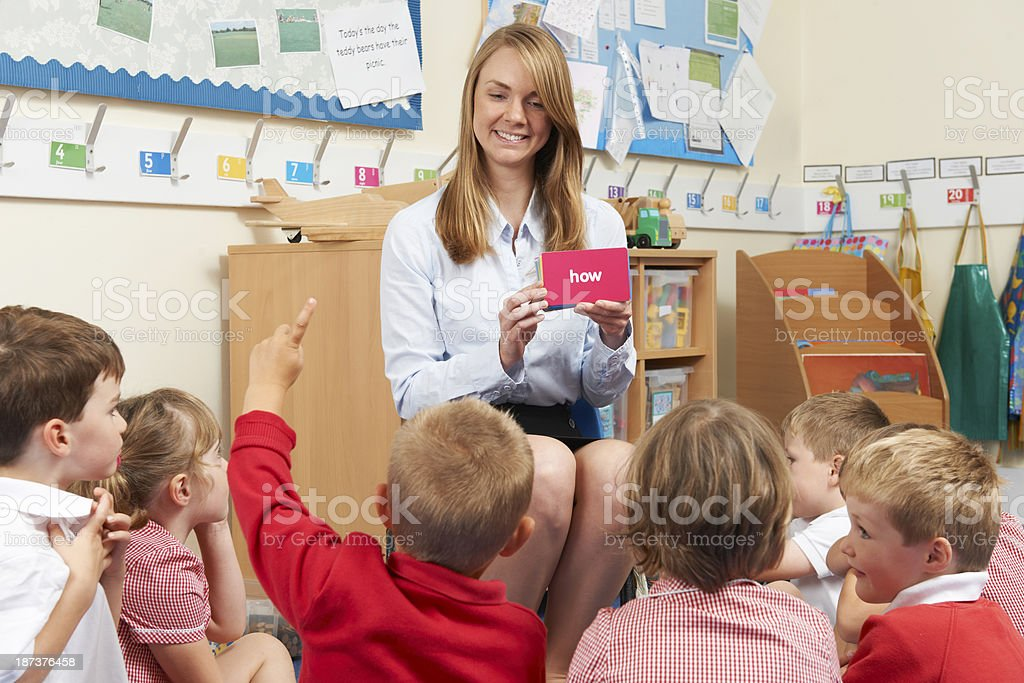 Female teacher showing flash cards to elementary students royalty-free stock photo
