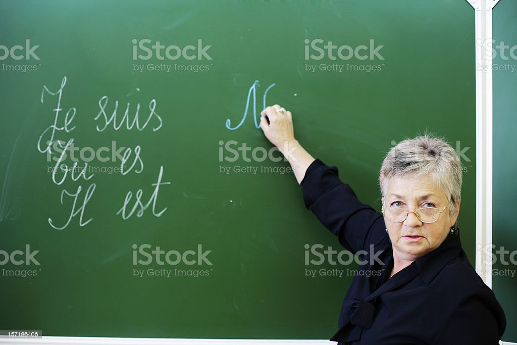 Female Teacher standing by blackboard, looking at camera stock photo