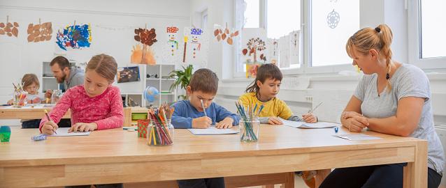 Female teacher supervising three children writing in their notebooks
