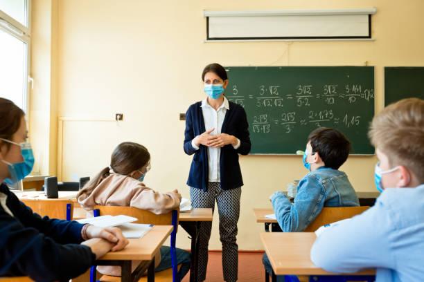 Female teacher teaching mathematics at school during Covid-19 stock photo