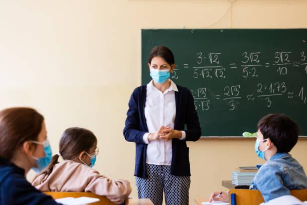 Lehrerin unterrichtet Mathematik in der Schule während Covid-19 – Foto