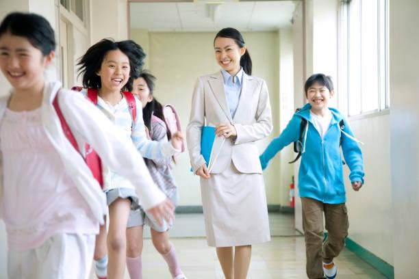女教師が廊下や小学生男性と女性はしゃぐを歩く - 小学校 ストックフォトと画像