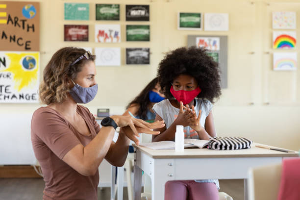 Female teacher wearing face mask helping a girl to sanitize her hands in class stock photo