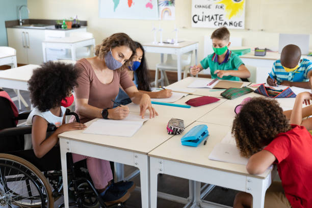 Female teacher wearing face mask teaching a disable girl in class stock photo