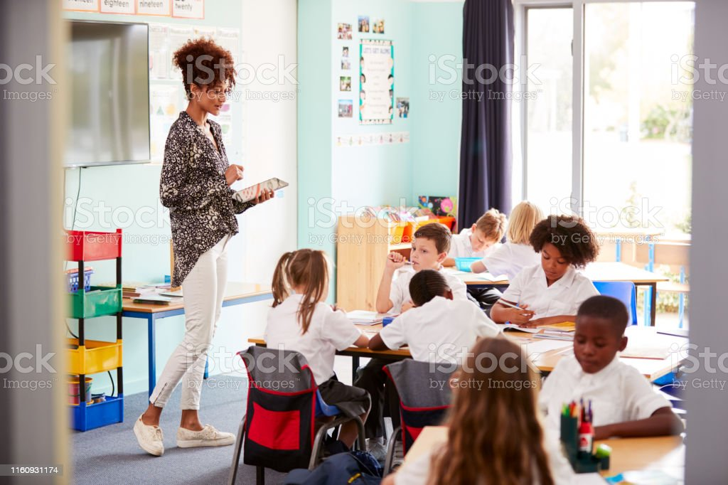 Female Teacher With Digital Tablet Teaches Group Of Uniformed Elementary Pupils In School Classroom Female Teacher With Digital Tablet Teaches Group Of Uniformed Elementary Pupils In School Classroom 20-29 Years Stock Photo