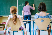 female teacher writes at the blackboard. rear view of two girls in front.