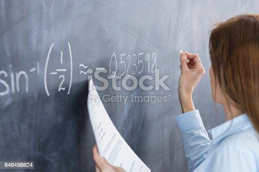 istock Female teacher writes math problem on chalkboard 646498624