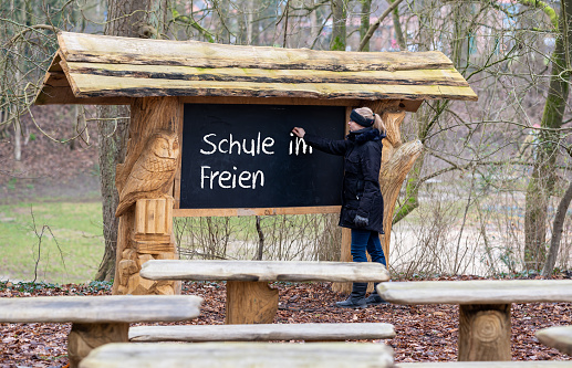 """Female teacher writes on a blackboard the German expression """"Schule im Freien""""(school outside). A classroom in the forest is qualified for teaching during the corona pandemic."""