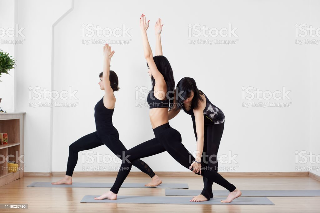 Young sporty attractive female team exercising yoga lesson with...