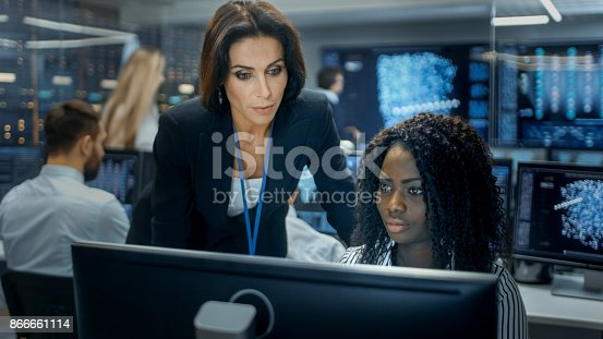 istock Female Team Leader Consults Young Computer Engineer. They Work in a Crowded Office on a Neural Network/ Artificial Intelligence Project. 866661114