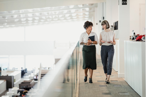 Two female professionals having a relaxed meeting while strolling along a raised walkway in an office auditorium.