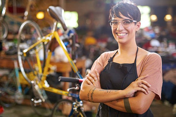 Female technician in her bicycle repair shop Female young  technician looking at the camera in her bicycle repair shop bicycle shop stock pictures, royalty-free photos & images