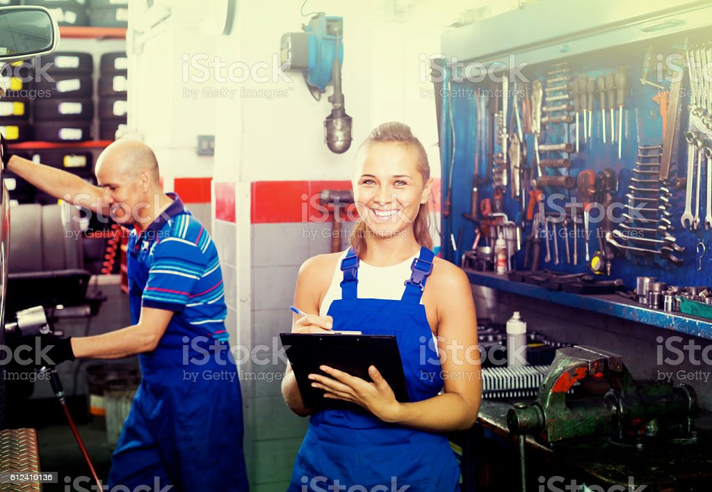 female technician in overalls holding clipboard  in car workshop stock photo