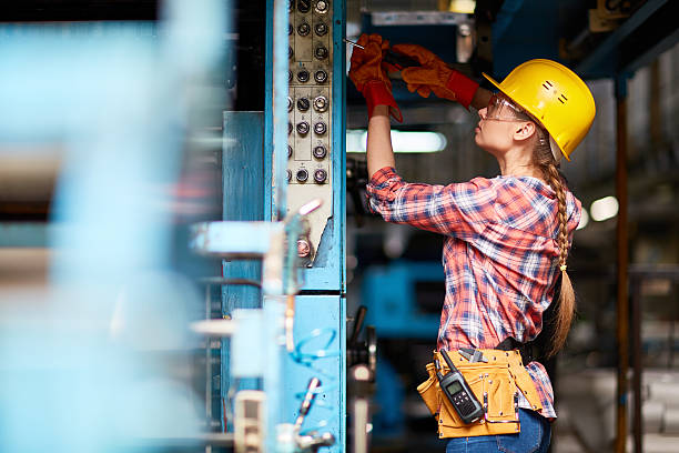 Female technician Female electrician or technician with screwdriver repairing machine at plant power occupation stock pictures, royalty-free photos & images