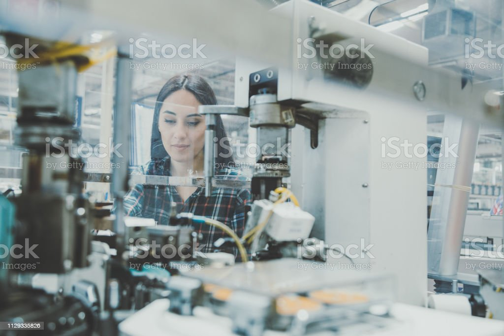 Professional young industrial factory woman employee working with...