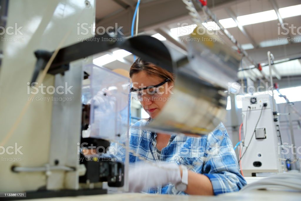 Female technician working with manufacturing equipment in a factory