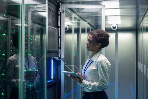 vrouwelijke technicus werkt op een tablet in een datacenter - datacenter stockfoto's en -beelden
