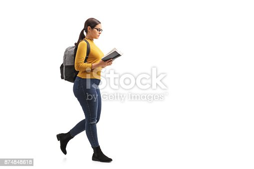 istock Female teen student reading a book and walking 874848618