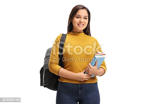 istock Female teen student with a backpack and books smiling 875284140