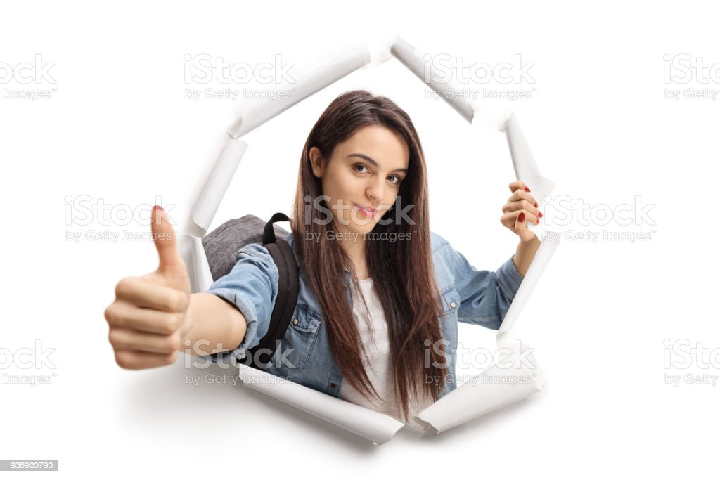 Female teenage student breaking through paper stock photo