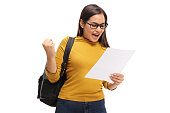 istock Female teenage student looking at an exam and gesturing happiness 867351550