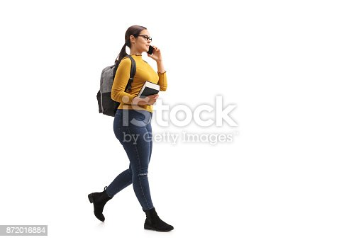 istock Female teenage student walking and talking on a phone 872016884